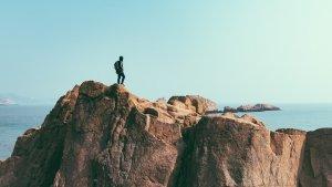 岩場にたたずむ男性登山者